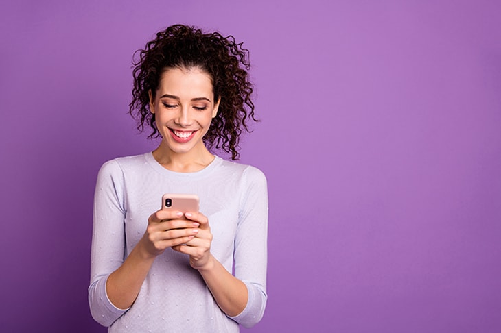 Woman smiling holding smart phone in front of a purple background.
