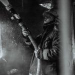 grayscale-photography-of-a-fireman-holding-a-hose-2704254